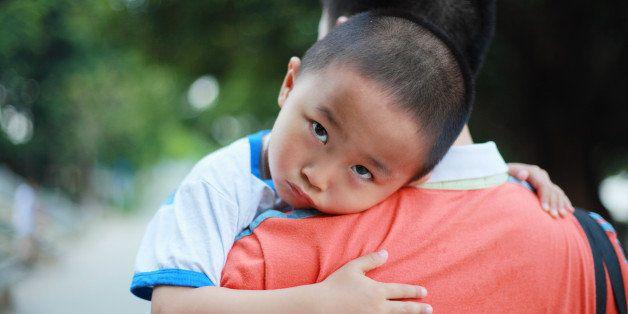 Unhappy boy on papa's shoulder.