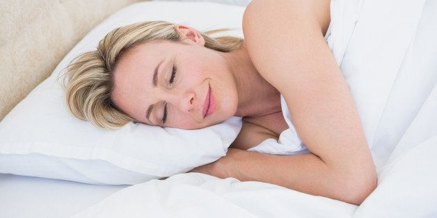 Smiling blonde woman resting in bed at home in the bedroom
