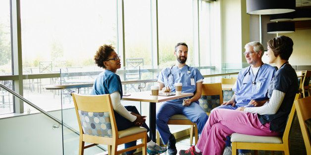 Smiling medical team in discussion during break in hospital employee lounge