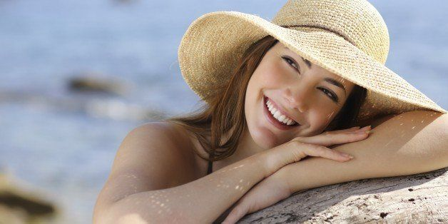 Happy woman with white smile looking sideways on vacations with the beach in the background