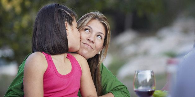 Daughter kissing mother on the cheek at garden dinner party