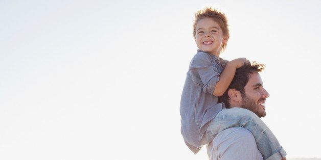 Father carrying son on shoulders on beach