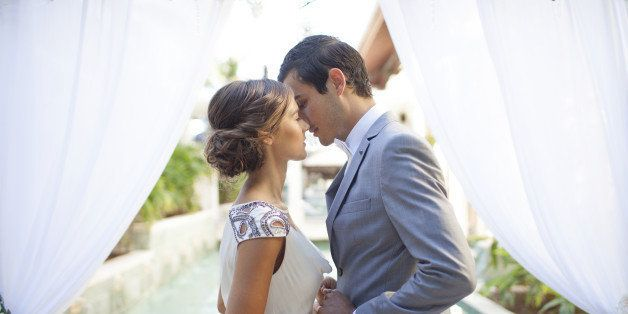 Bride and groom kissing at wedding alter