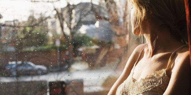 Young woman looking out of window in home