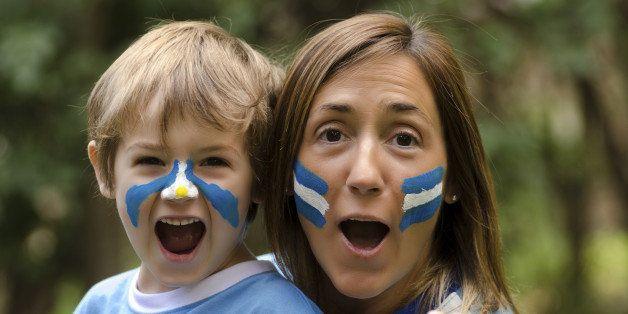 Mama e hijo, festejando un gol del seleccionado argentino. Pintados con la bandera argentina y utilizando la camiseta del mundial 2014.