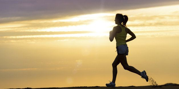 Woman running alone on beautiful sunset in the beach. Summer sport and freedom concept. Athlete training  on dusk.