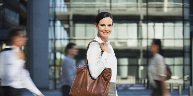 Smiling businesswoman outside urban building