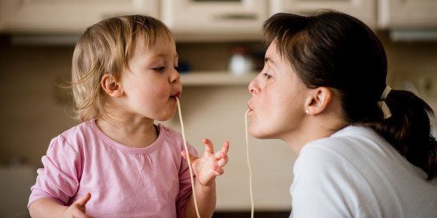 Mother and her little child sucking together spaghetti noodles.