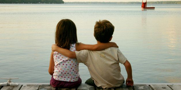 Boy and girl sitting on dock front of sea.