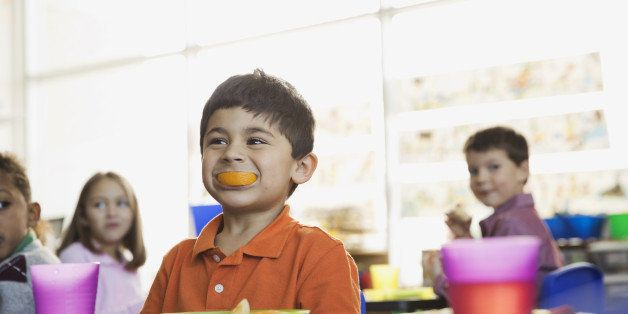 Playful boy holding orange slice in mouth at school at snack time