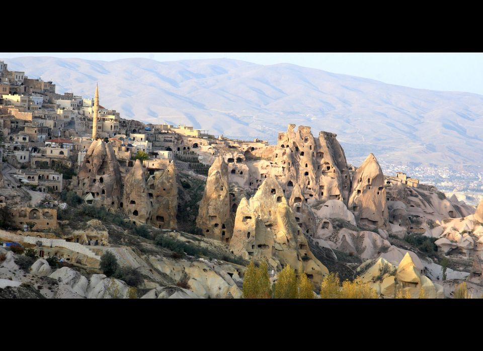 Ancient rock houses intermingled with modern houses in Cappadocia, Turkey.