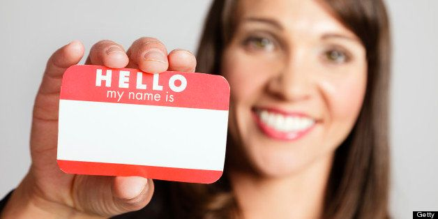 A pretty young woman holding a 'Hello My Name Is' name tag against a white background.