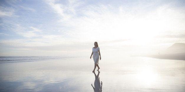 Woman walking alone on a misty beach