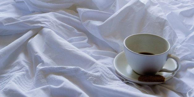 Coffee cup and cookie on bed
