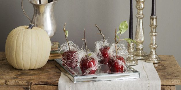 A platter of candied apples with spun sugar, candles, a white pumpkin and decorations for a Halloween Party