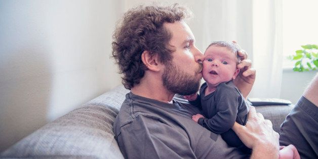 Young bearded dad kissing his 10 days newborn baby while relaxing on a couch at home. Both are wearing grey tops. Baby is very alert and have open eyes. TV remote control and window in background. Horizontal backlit waist up shot with copy space.