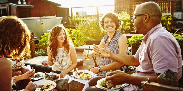 Laughing group of friends sitting together sharing dinner and wine in rooftop garden on summer evening