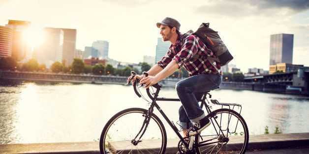 A young man commuting in an urban city environment on his street bicycle, a waterproof bike bag on his back. This is the Eastbank Esplanade in Portland, Oregon, that follows along the Willamette river. Downtown is visible across the water, the sun shining brightly between the buildings. Horizontal with copy space. In-camera lens flare.