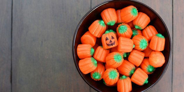 Bowl of pumpkin shaped Halloween candy. One has a jack o' lantern face.