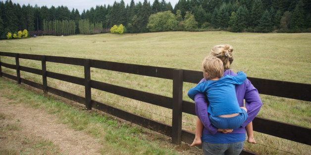 Woman carries son along wooden fence.