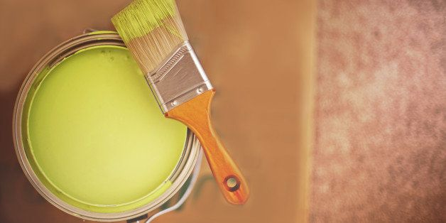 Green paint bucket with paint brush on cardboard.