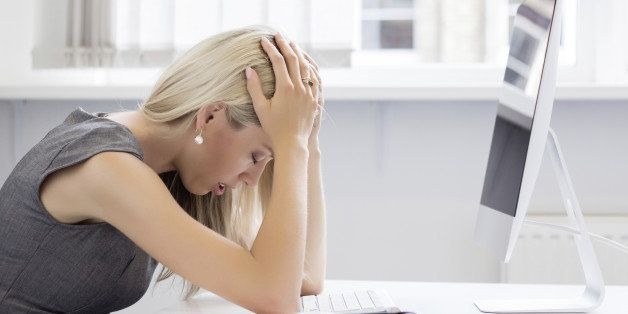 Overworked and frustrated young woman in front of computer in office.