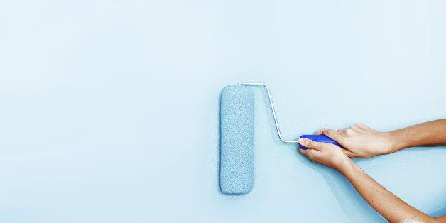 Hands painting the wall with a roller brush