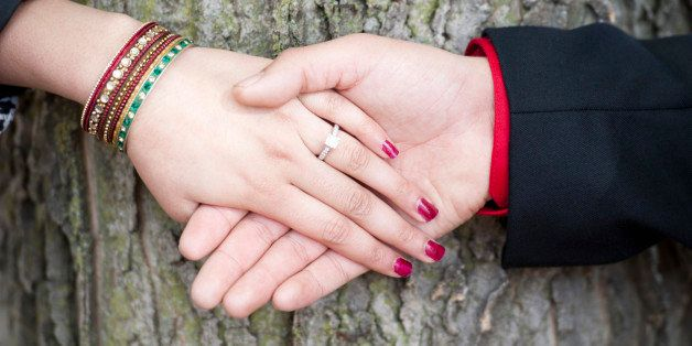A young Indian couple's engagement hands on a sunny day outdoors.