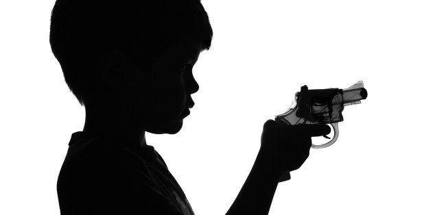 B&W Silhouette of a boy holding a toy gun