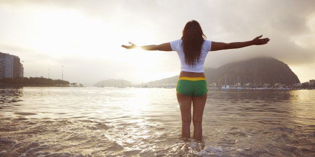 Mature woman with arms outstretched on Botafogo beach, Rio De Janeiro, Brazil