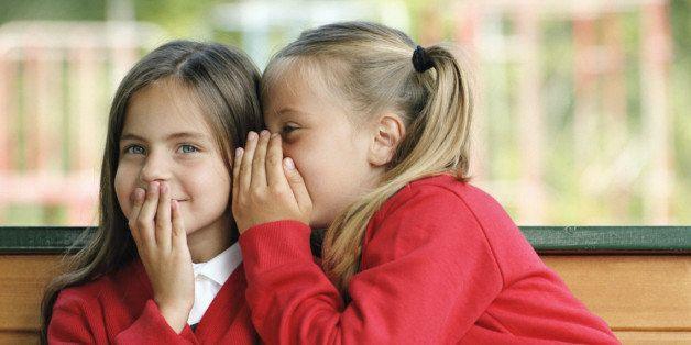 Two girls (6-8) sitting on bench whispering