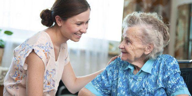 Elderly woman on wheelchair with a nurse