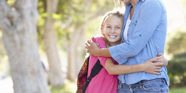 Mother And Daughter Walking To School On Suburban Street Hugging