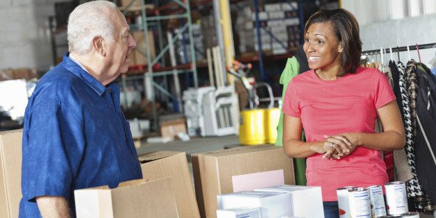 Young woman and older man working at food and clothing donation center.