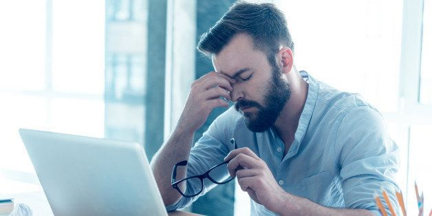 Frustrated young beard man massaging his nose and keeping eyes closed while sitting at his working place...