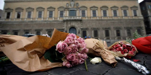 Flowers are laid in front of the French embassy in Rome, Saturday, Nov. 14, 2015. French police on Saturday hunted possible accomplices of eight assailants who terrorized Paris concert-goers, cafe diners and soccer fans with a coordinated string of suicide bombings and shootings in France's deadliest peacetime attacks. (AP Photo/Gregorio Borgia)
