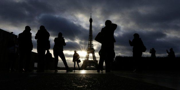 Tourists visit the site of Eiffel Tower which remained closed on the first of three days of national mourning in Paris, Sunday, Nov. 15, 2015. Thousands of French troops deployed around Paris on Sunday and tourist sites stood shuttered in one of the most visited cities on Earth while investigators questioned the relatives of a suspected suicide bomber involved in the country's deadliest violence since World War II. (AP Photo/Amr Nabil)