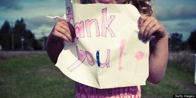 Little girl in pink fairy dress, holding up a child's drawn thank you sign.