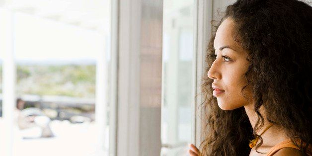 Woman daydreaming at window