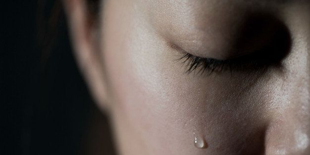 Young woman crying with tear drop.