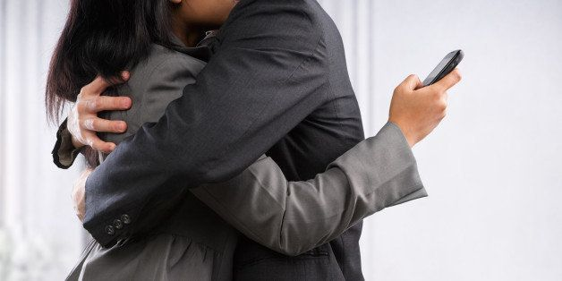 Business couple hug yet the woman still using cell phone, can be concept for busy lifestyle of cheating