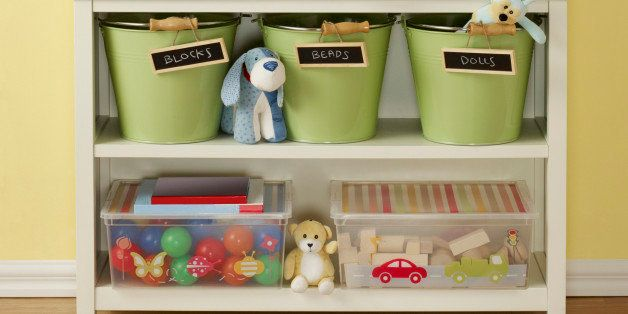 Interior of a child's play room showcasing a white shelf photographed on a wood laminate floor against a yellow painted wall with two hanging blank canvas that have paths for dropping in other art work. White shelf suggests storage ideas, it has three chalk labeled buckets that can store various kid items and two plastic containers with lids one has blocks and the other plastic balls.