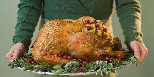 Man holding Thanksgiving turkey on decorated platter