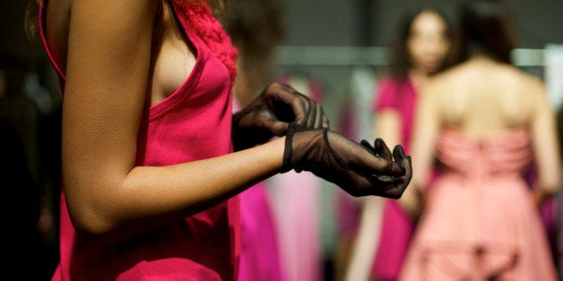 A fashion model puts on a glove while waiting backstage during Fashion Week L.A.