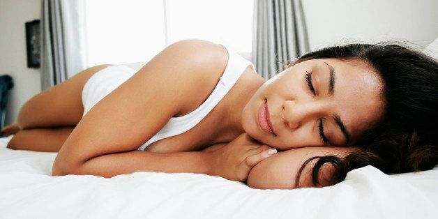 Hispanic woman sleeping on bed