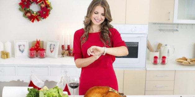Woman holding roasted turkey for christmas dinner, looking at her watch.