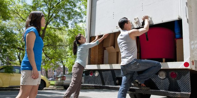 group of friends standing at the back of small moving truck, lifting up rear door, truck filled with moving boxes and furniture, urban environment
