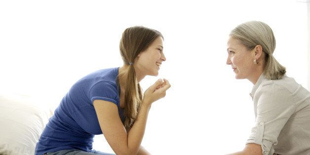 Mature mom and teenage daughter talking, bonding, and smiling with each other