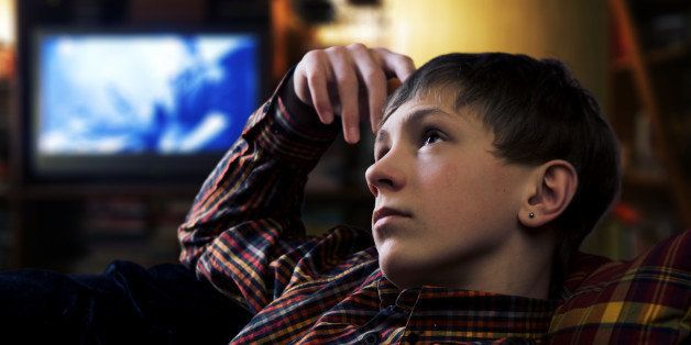 Teenage boy lies at pillows and drreaming on the background of evening home interior