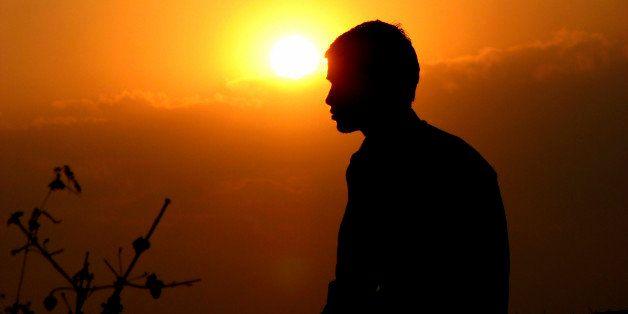 An Indian meditating at sunset